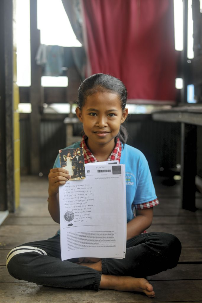 10 year-old girl sits on her floor smiling with a letter and picture from her sponsors.