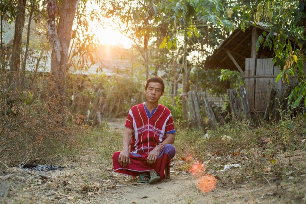 Moue-ae, Thidarat's father sits cross legged, outside his home, with a serious look on his face.