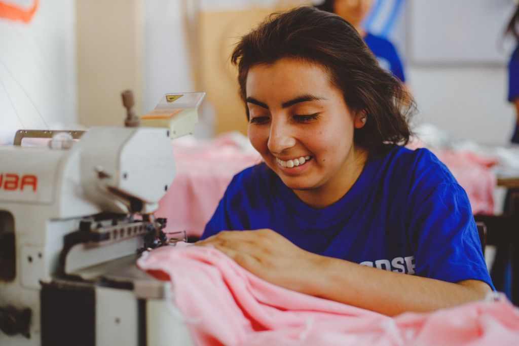 A girl wearing a blue shirt smiles as she sews pink cloth on a sewing machine.