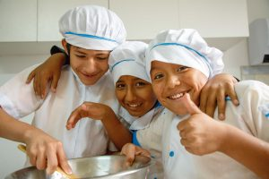 Three boys wearing baker's caps smile with their arms around each other, one giving a thumbs up while another holds a large kitchen bowl.
