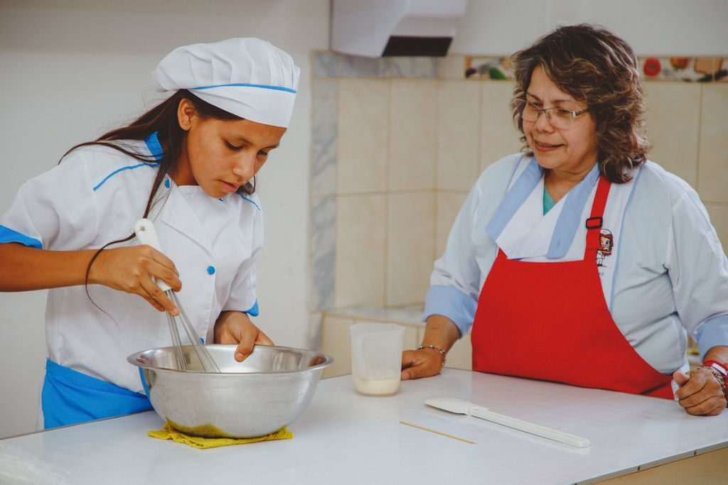 A girl in a white coat and white baker's cap uses a whisk in a metal bowl while a woman in a red apron watches.