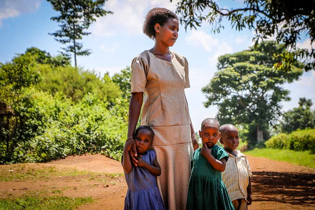 A woman in a tan dress stands, looking off into the distance, surrounded by three young children.