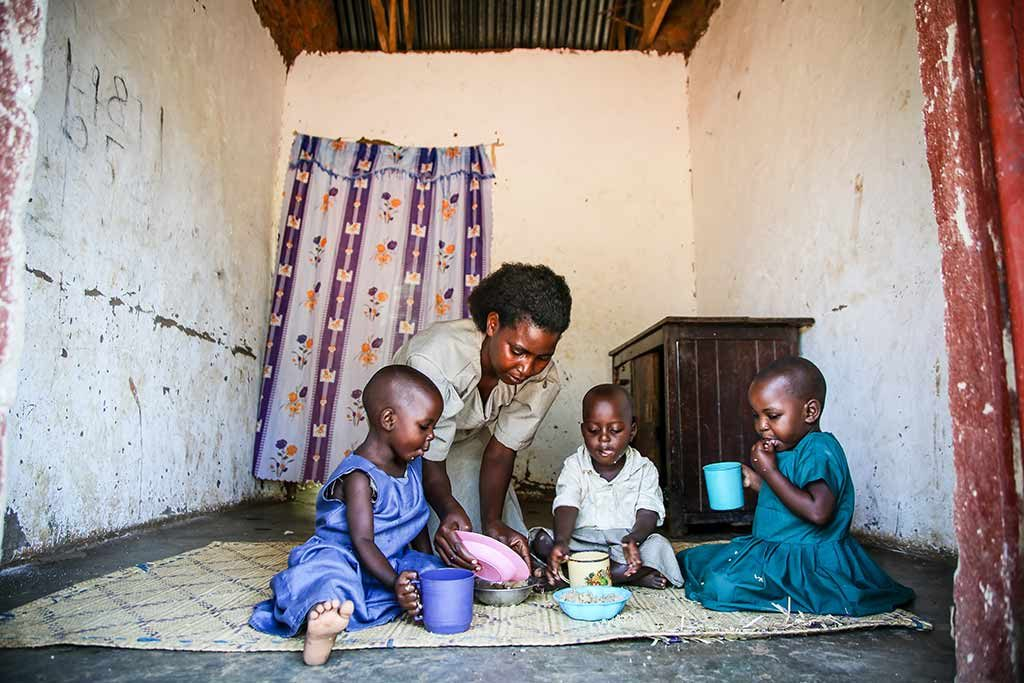 Three children sit on a mat inside a small room eating and drinking, while their mom helps.