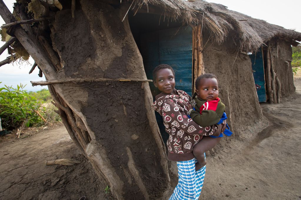 A young girl holds a baby in her arms while leaning against a home made from mud and sticks with a thatched roof.