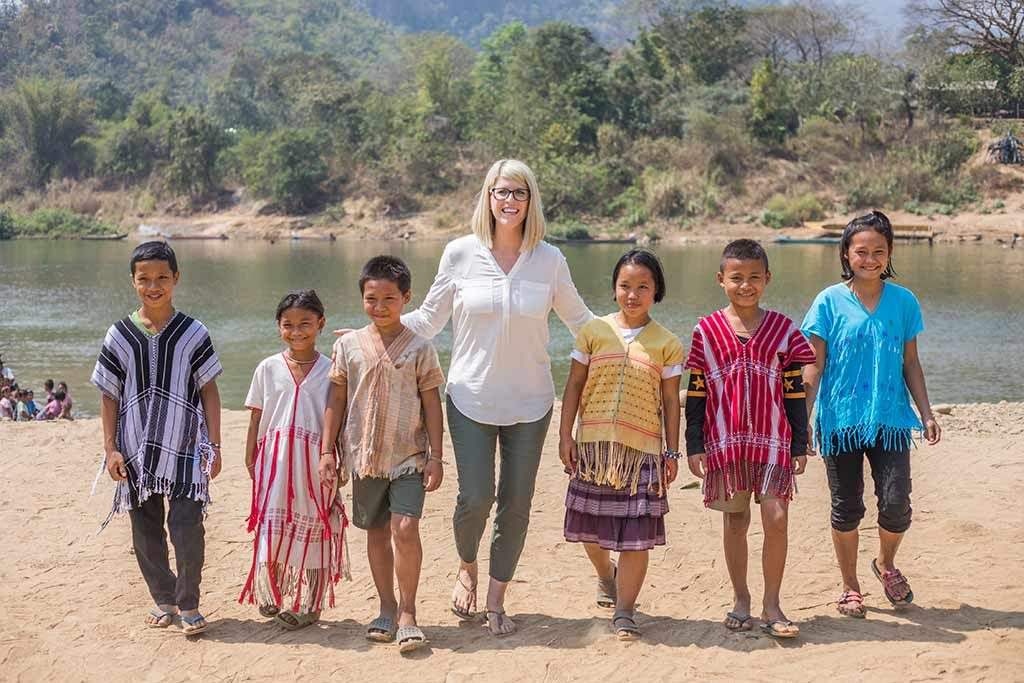 A woman in white stands in the middle of a group of children wearing colorful tribal clothing in front of a river and mountains.