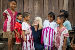 A blonde woman in a blue shirt crouches, surrounded by six children wearing colorful tribal shirts