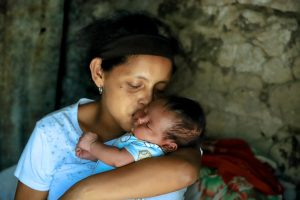 An El Salvadorian mother holds her baby close and kisses him the cheek.