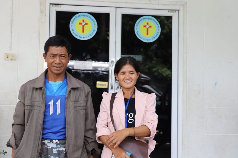 The happy parents of the sponsored boy who has been rescued from the cave in Thailand standing outside of the church where their son attends the Compassion program.