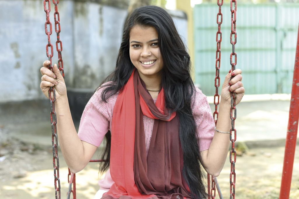 18 year-old girl smiles while sitting on a red swing.