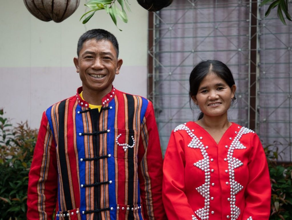 A couple smiles wearing brightly colored traditional clothing.