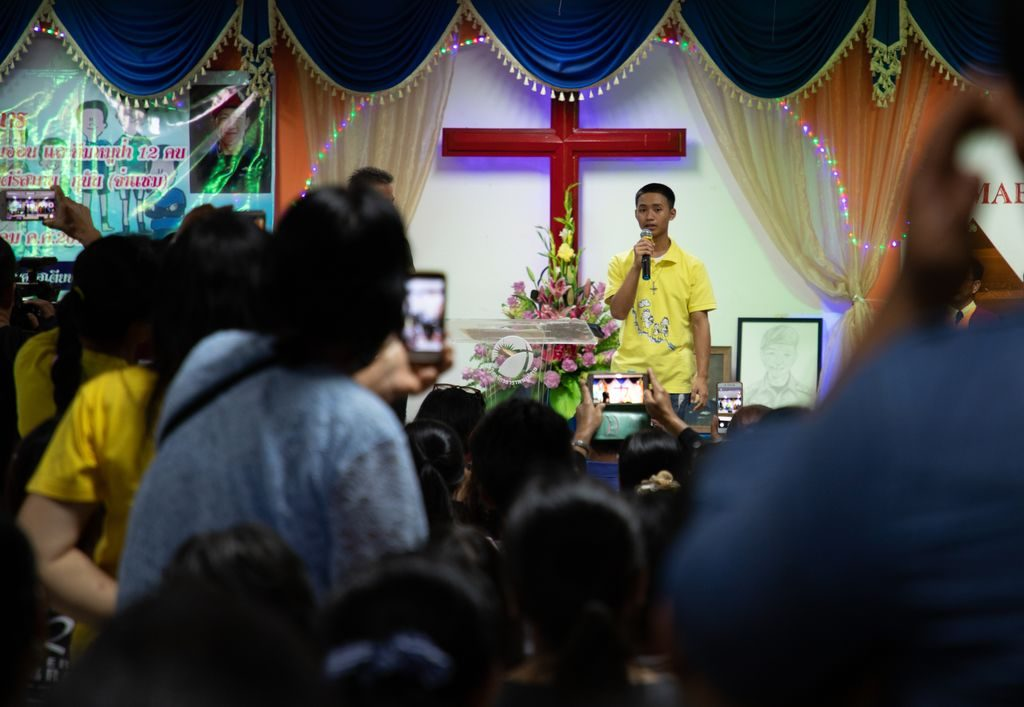 A boy in a yellow shirt holds a microphone and speaks to a group at the front of a church.
