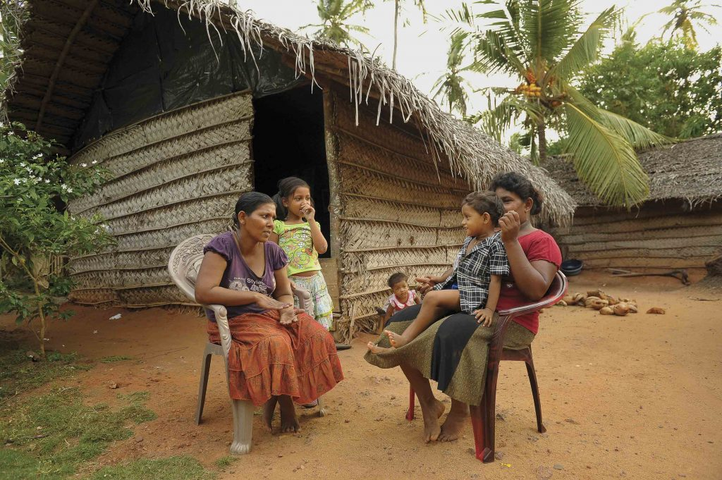 There are Sri Lankan women and children sitting in chairs outside of a hut/home talking.