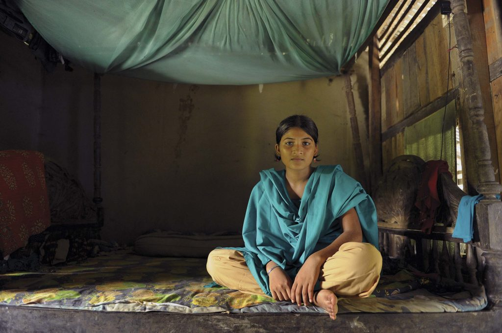 Project girl, child, teenager, teen, youth, Laboni Akter, age 14 years old, sits on the floor, mat, blanket, inside her bedroom, a room of her home, with a large green netting, mosquito and malaria prevention netting hanging bundles up above her head. She is wearing a green shirt and scarf, school uniform shirt and tan, beige pants.