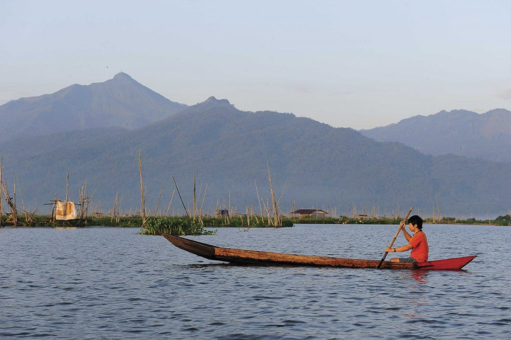 Andistya Han Putra, a teenager, teen, youth, 18 year old project boy, wearing an orange shirt, sits in a canoe, boat, long narrow boat, holding a long bamboo pole in his hands paddling, as the boat floats along river, water. Mountains show in background scenery, landscape.
