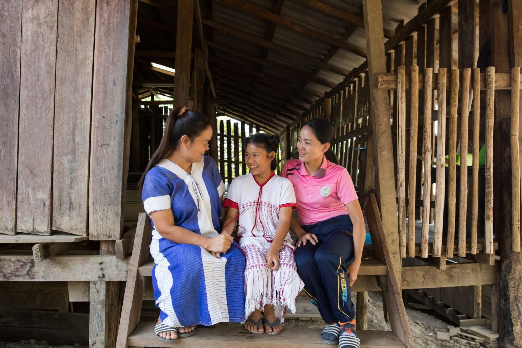 Kannika, centre director, and Nat, mentor, are two of the women at the Compassion centre who are building into Thidarat's life. They sit on the steps laughing together.