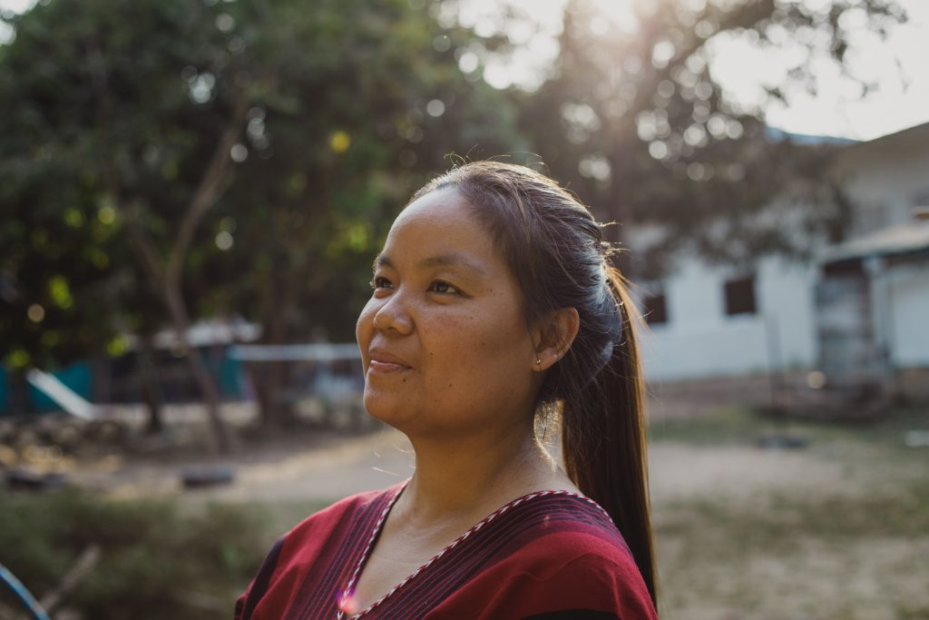 Kannika smiles off to the side in front of the Compassion centre that she directs.