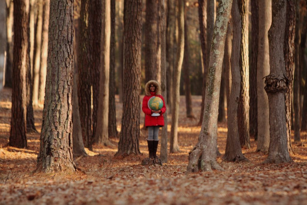 Girl stands in the woods wearing a red coat and a hood, holding a globe.