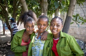 Three young women in Ethiopia with their arms around each other, smiling for the camera.