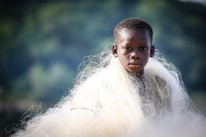 A boy has a white fishing net wrapped around his shoulders. The background is blurry.