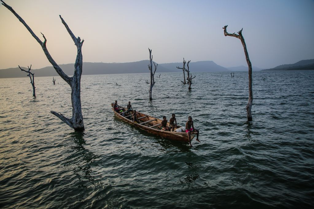 A group of boys sit in a wooden boat on choppy waters, surrounded in dead trees sprouting through the water.