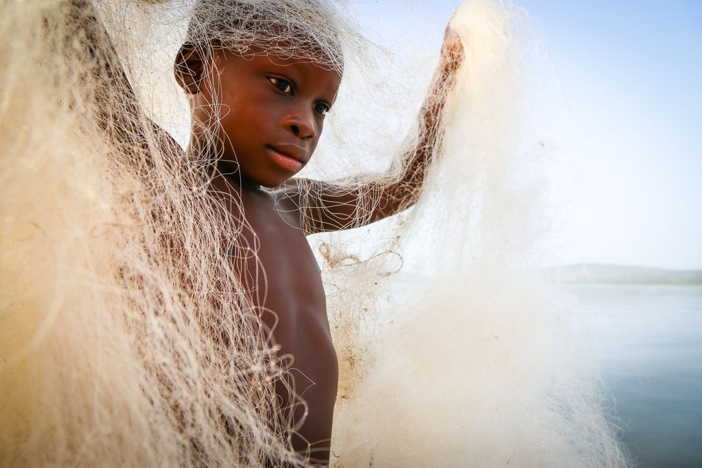 A little boy holds up a fishing net around him.