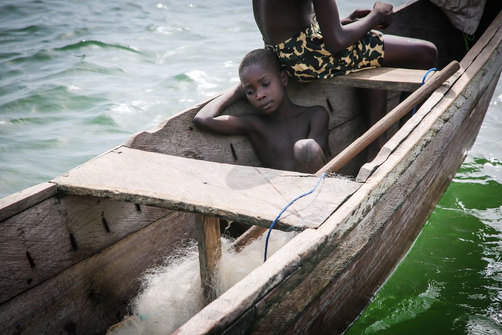 Little boy sits on the floor of the wooden fishing boat, looking sad.