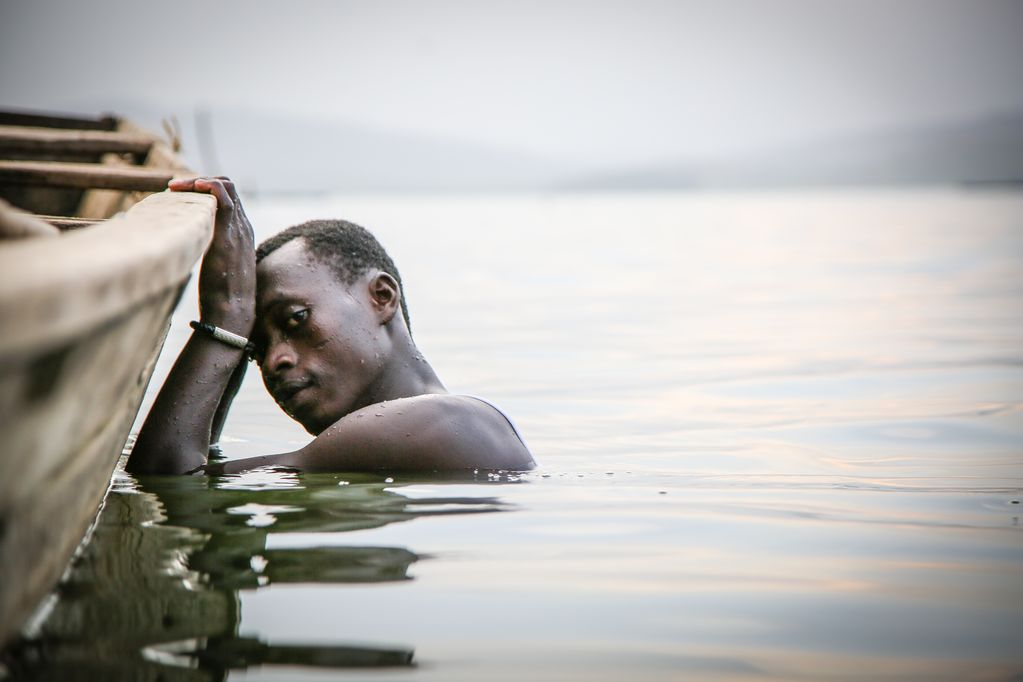 Boy in submerged in the water, his hands are holding onto the edge of the boat, as he looks at the camera with a defeated look in his eyes.