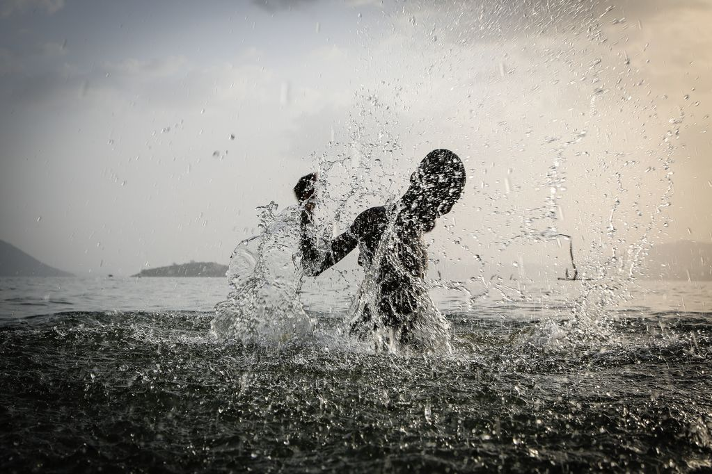 A boy splashes in the water.