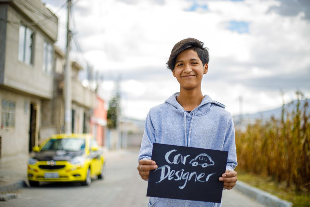 "A teenage boy stands infront of a yellow car holding up a sign that reads, "" Car Designer."""