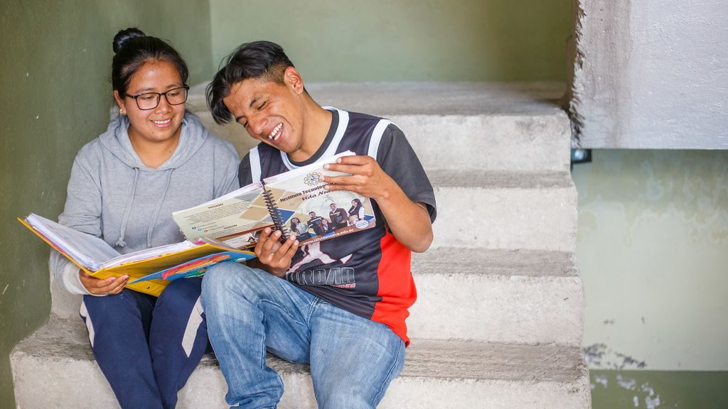 A teen boy and girl laugh together while reading books on the steps of their Compassion centre.