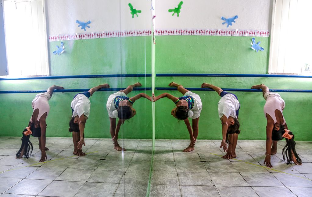 3 girls dance in a green dance studio in front of a large mirror.