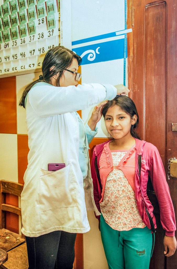 A girl stands against a wall smiling being measured by her doctor.