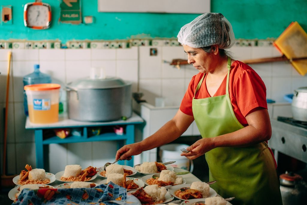 A woman in an orange shirt and a hair net is in a kitchen making food for the project kids.