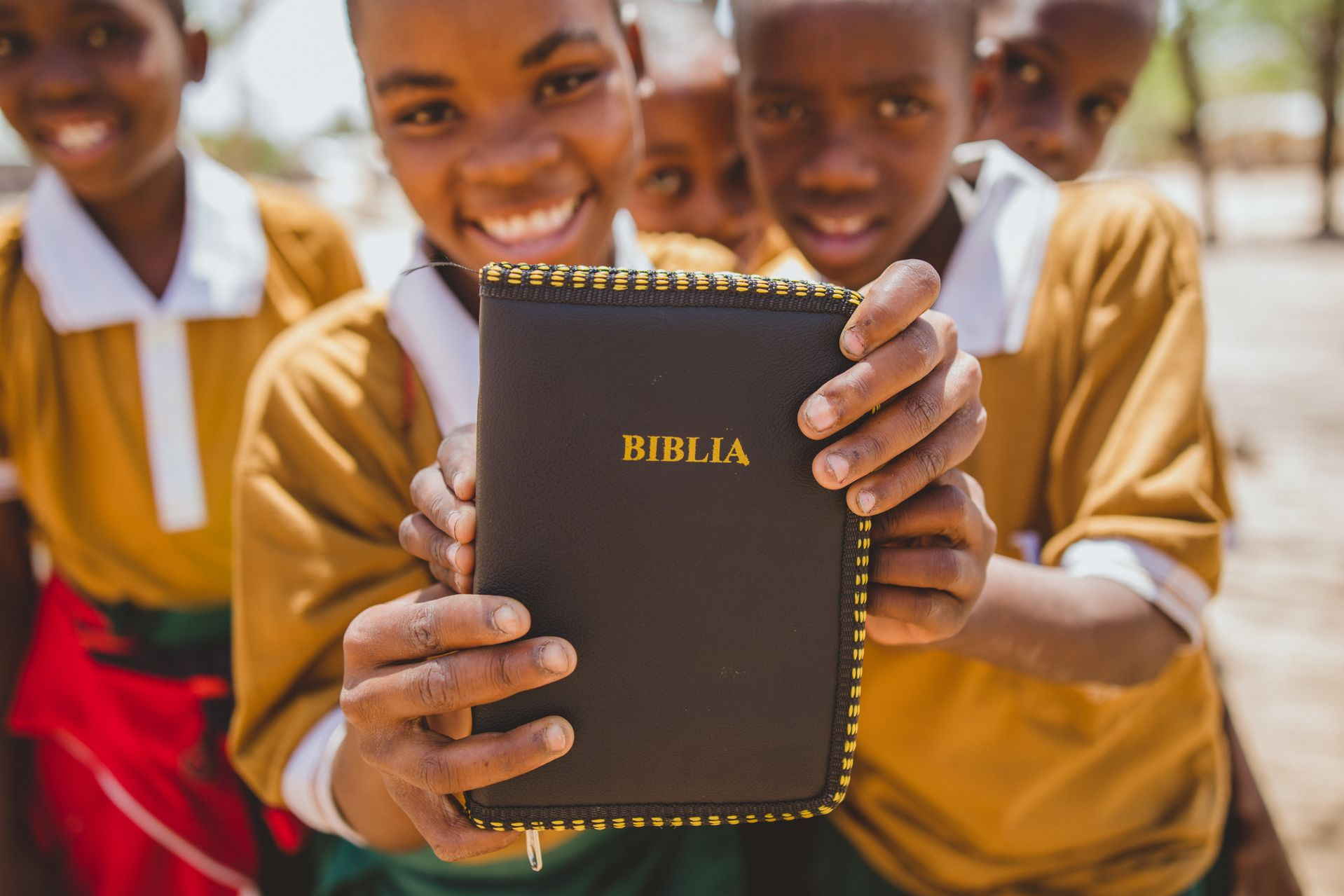 Two smiling children in Tanzania hold up a brown and yellow Bible.
