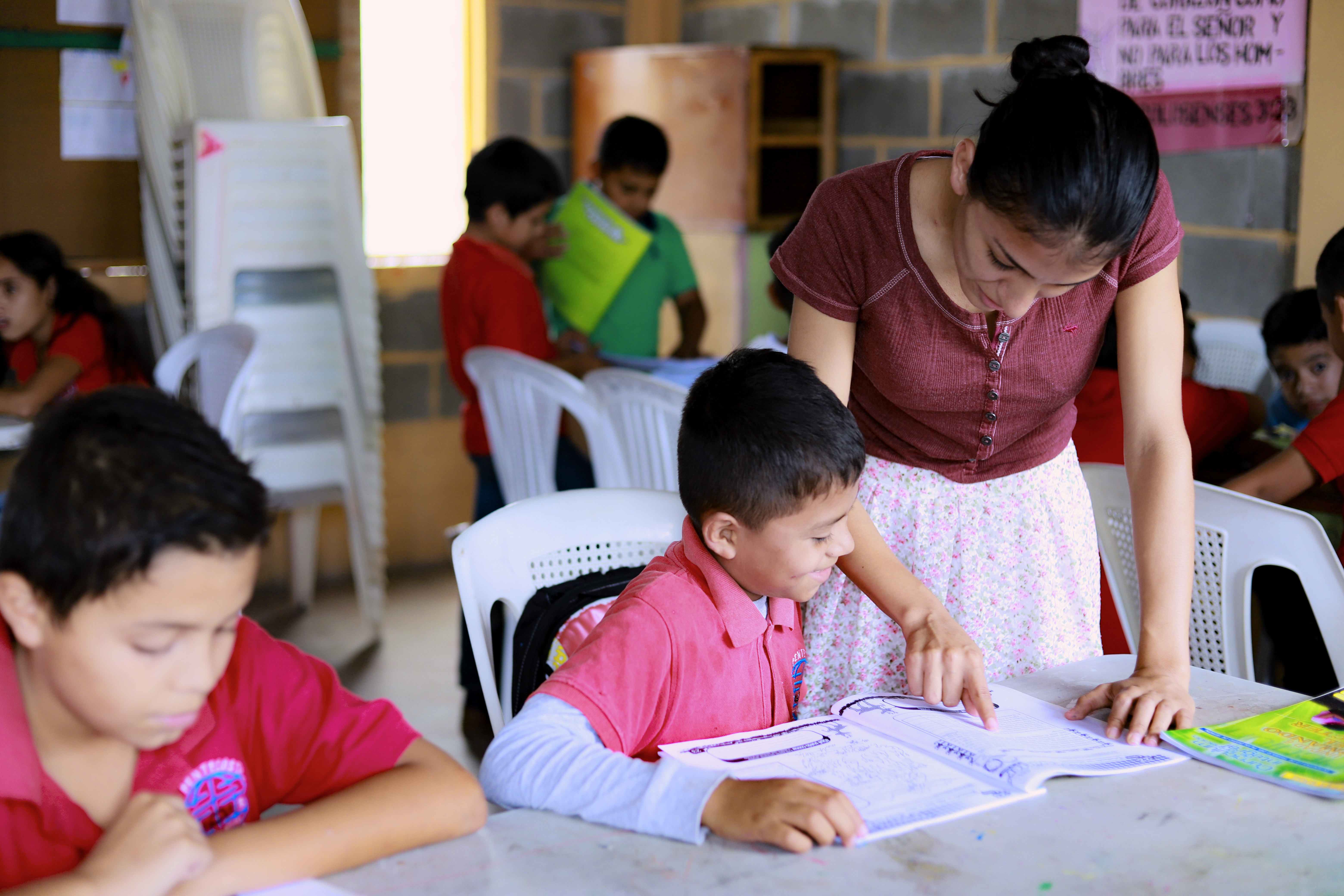 A tutor, Debora, helps a young boy, her student, with a letter he is composing in his notebook.