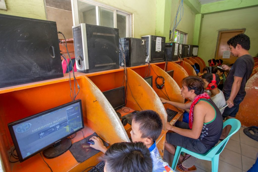 Children and young adults are pictured in orange cubicles in an internet cafe.