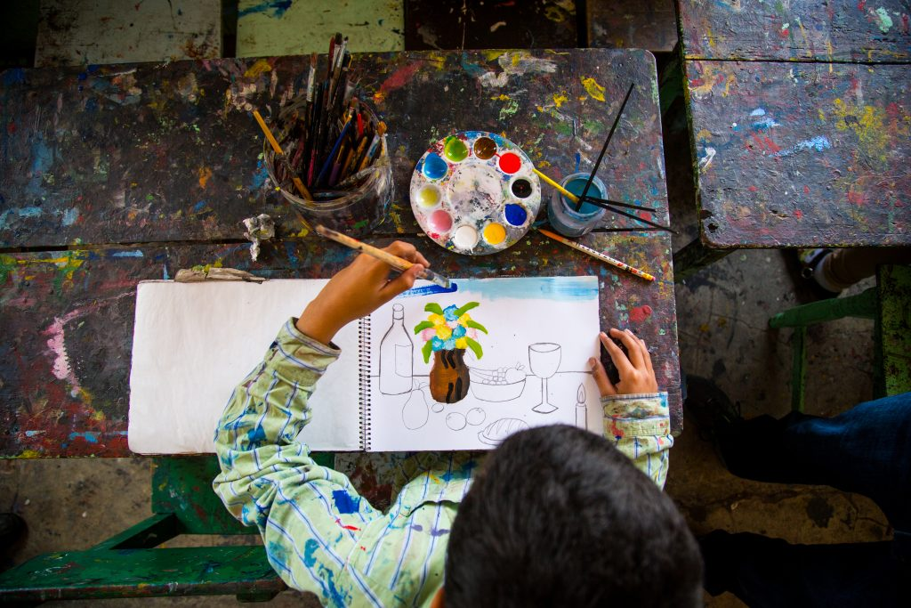 An overhead shot of Hector working on a painting. He is painting a flower vase.