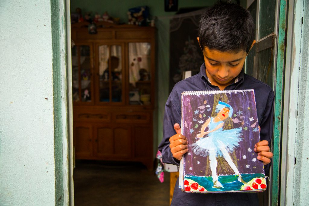 Hector, a young boy, stands in a doorway, looking down at his painting of a ballerina, which he holds up to his chest.