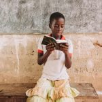 A girl in a white shirt and a yellow skirt sits on a wooden table and reads a book.