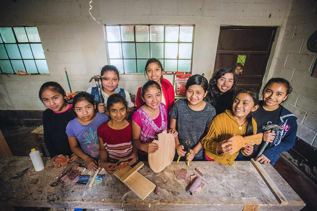 A number of teenage girls stand in a room holding wood items they have made, smiling at the camera.
