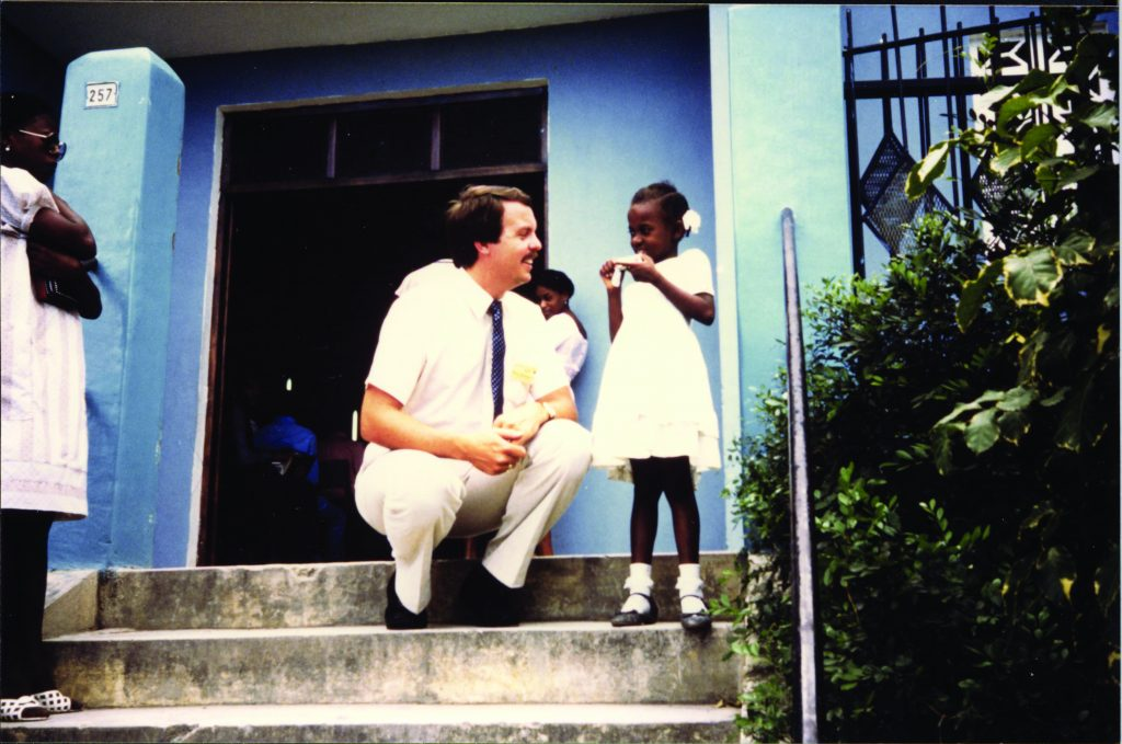 Barry Slauenwhite kneels to eye level with a Haitian girl on the steps of a church building.