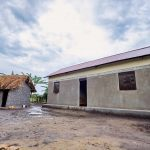 Two homes side by side, one made from mud and one made from concrete