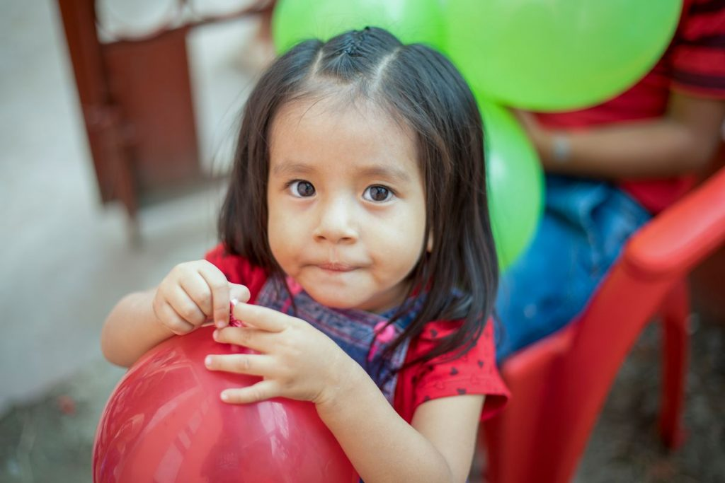 Little girl wearing a red shirt is tying up a red balloon after blowing it up!
