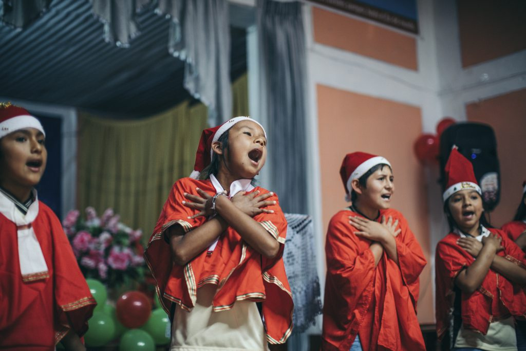 Children singing songs on the stage with santa hats, crossing their arms!