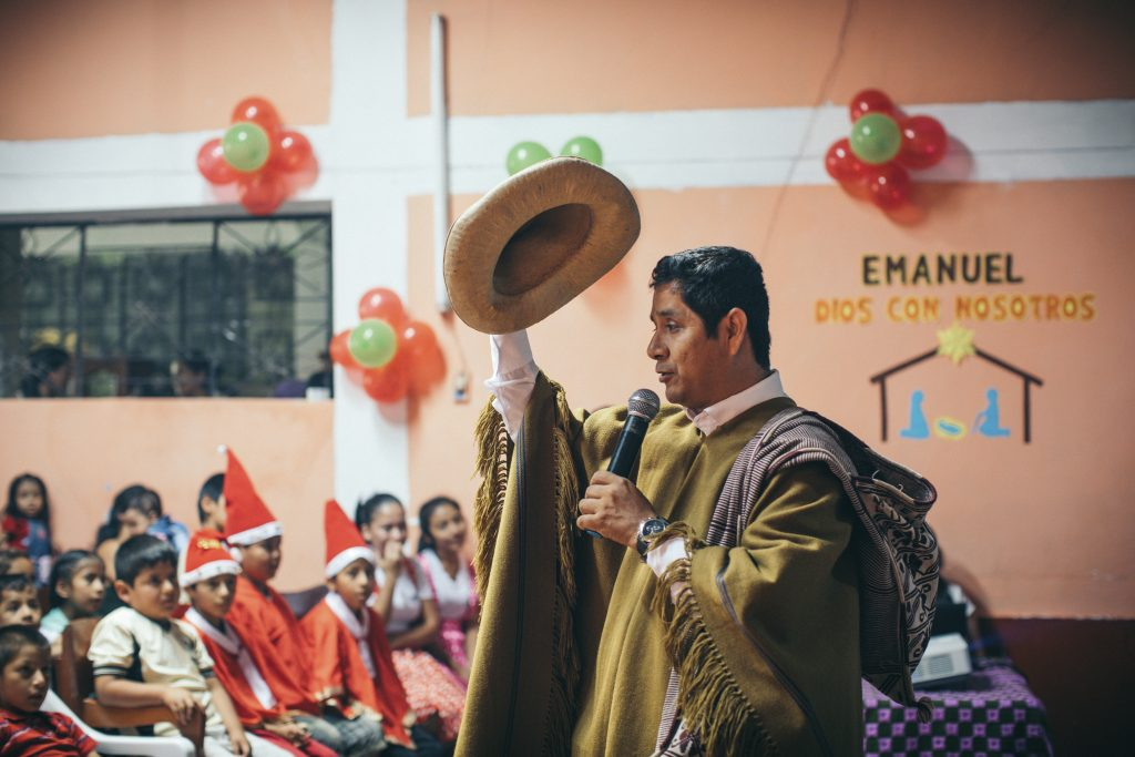 A pastor wears a traditional outfit, tipping his hat as he shares a Christmas message with the children.