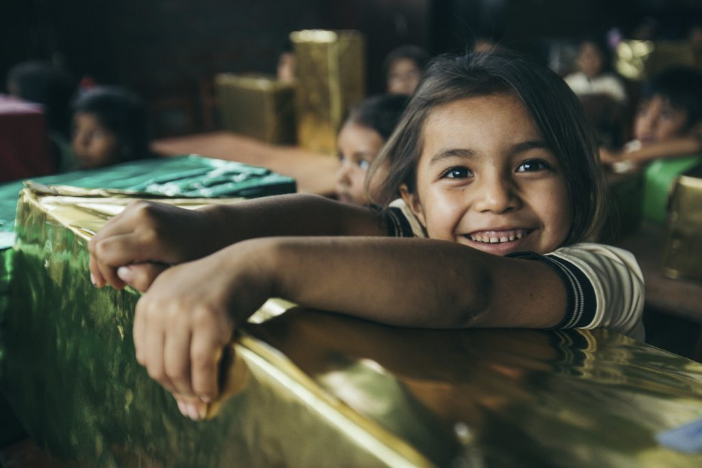 Little girl has a big smile on her face as she leans over her gold-wrapped present