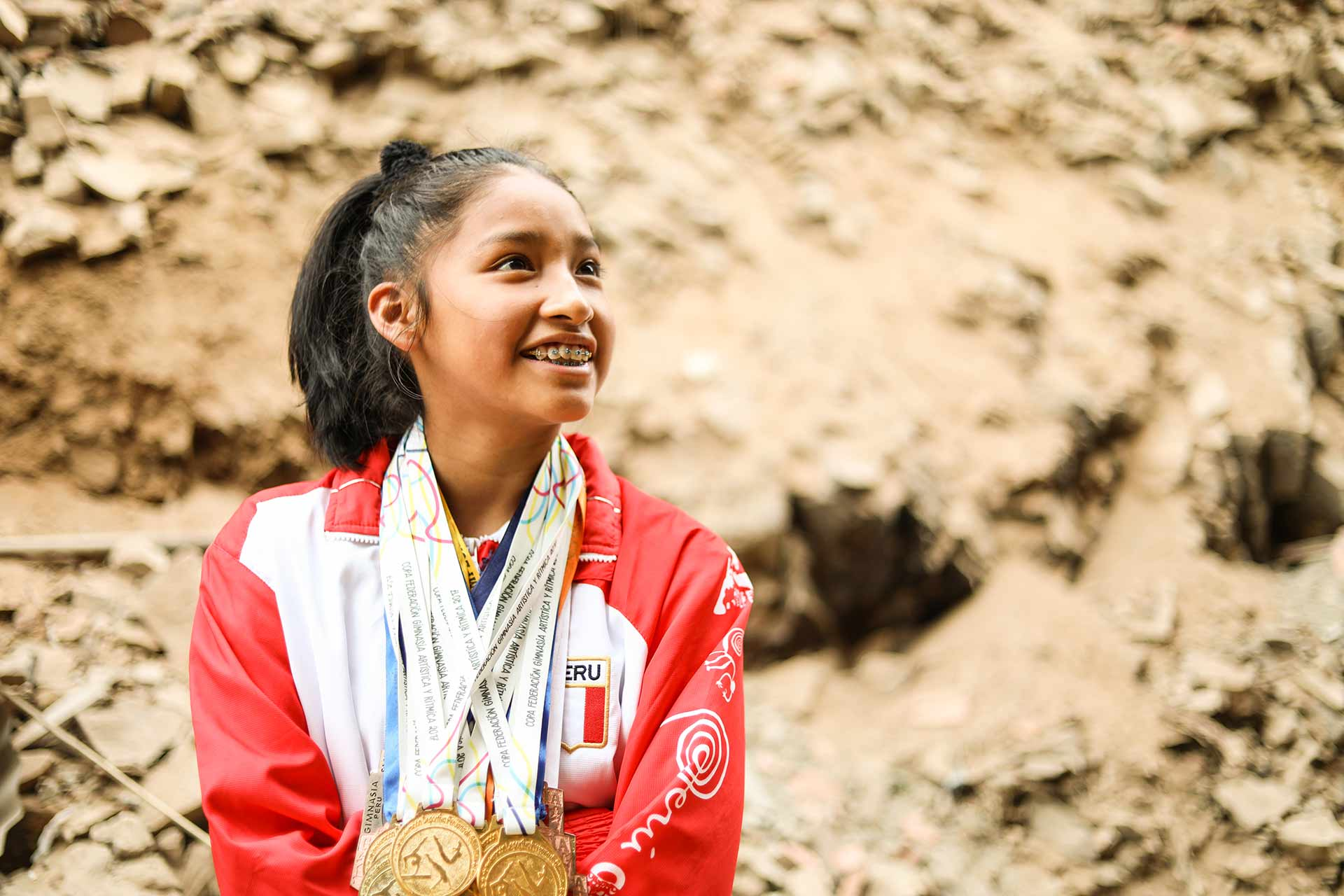 A girl wearing a red and white jacket has multiple gold medals around her neck. She smiles, looking up and to the side.