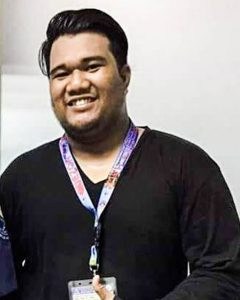 A picture of a Filipino man in a black sweater giving a thumbs up.