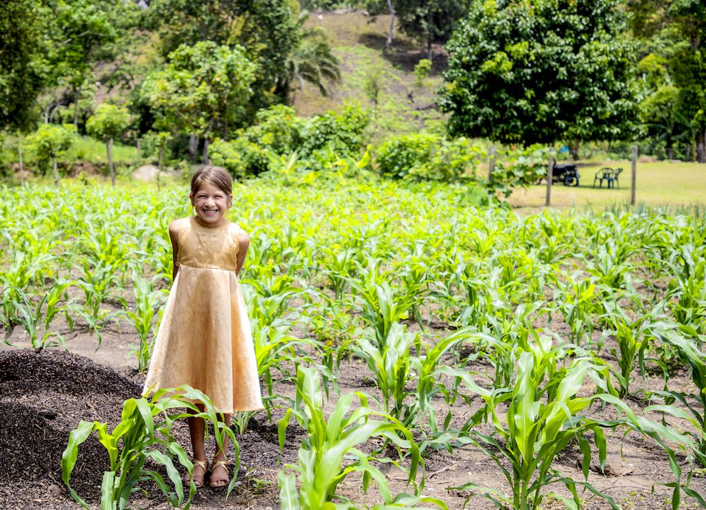 Little girl wearing a yellow dress stands beaming in a green field.
