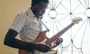 A Ugandan teenage boy plays an electric guitar. He stands in front of a window